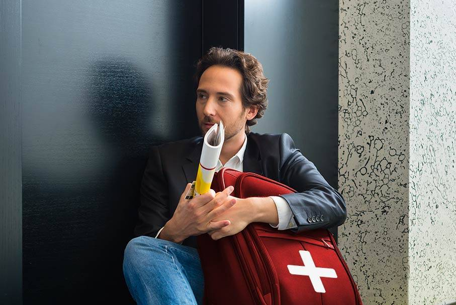 A young man with Google+ red suitcase sits waiting in front of a door