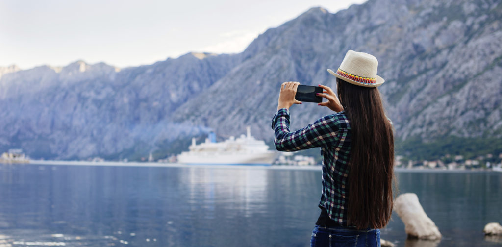 girl taking photo on smartphone of cruise liner