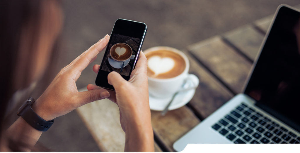 Woman taking a picture of a coffee cup with her smart phone while sitting at a coffee shop.
